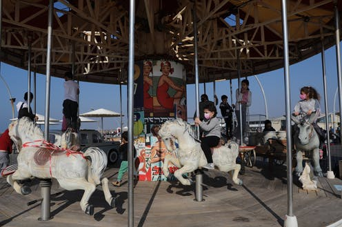 Children in Tel Aviv, Israel, playing on a merry-go-round, February 2021.