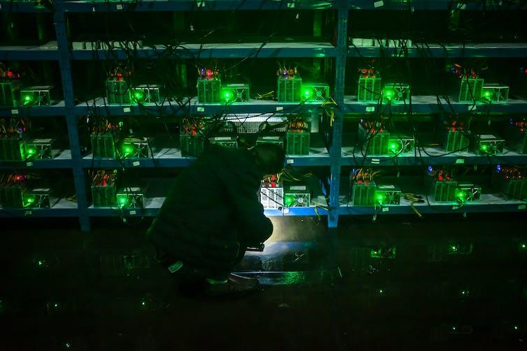 A worker inspects a bitcoin mining machine.