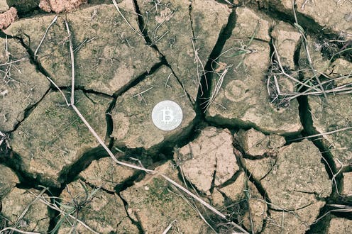A silver bitcoin on parched, cracked soil.