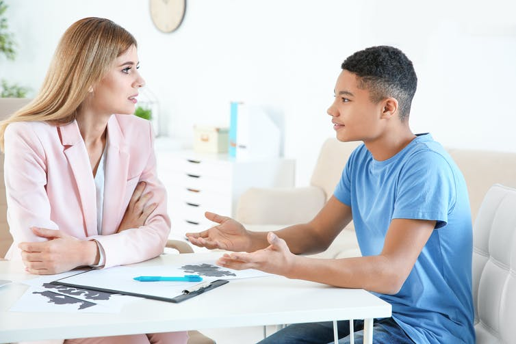 Teenage boy talking to woman in office