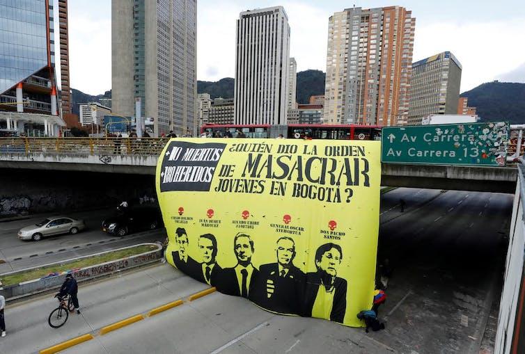 Pancarta de denuncia colgada de un puente sobre una autopista en Bogotá (Colombia)