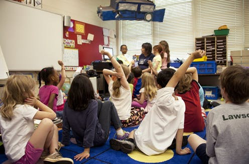 Kids raise their hands in a middle-school classroom. Children look about 7-years old.