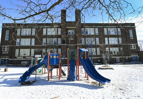 A school in winter, the empty playground is in the foreground.