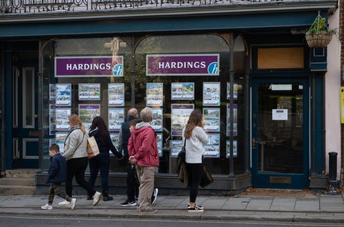 People gather outside looking at an estate agent's window