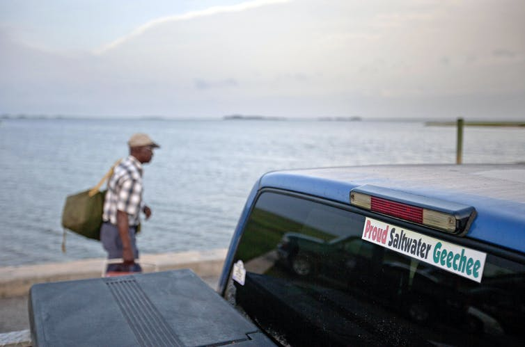 A sticker celebrating the Geechee heritage is seen on a pickup truck as passengers board a ferry.