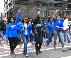 Several African American women dressed in blue walk together.
