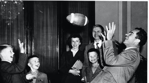 Richard Nixon, tossing a football with boys.