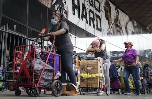 Pedestrians wait in line with carts to collect fresh produce and shelf-stable pantry items outside Barclays Center in New York City