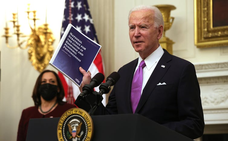 Joe Biden holds a copy of the national COVID-19 strategy