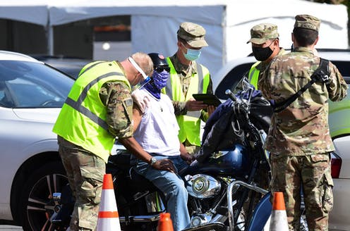A man on motorcycle gets a vaccine shot from National Guard troops.