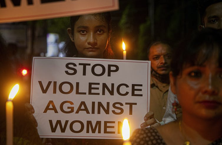 A woman carries a placard that reads 'Stop violence against women'.