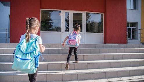 Two young girls walking up the school steps.