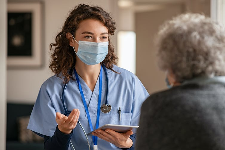 A health-care worker wearing a mask talks to an elderly person.