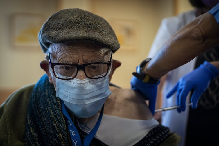A man receives the Pfizer vaccine at his aged-care residence in Spain.