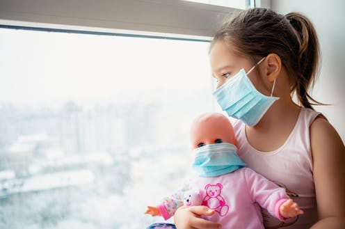 Girl wearing mask looking out of window holding doll wearing mask