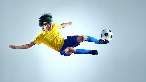 Un futbolista en el aire con la equipación de Brasil chuta un balón.