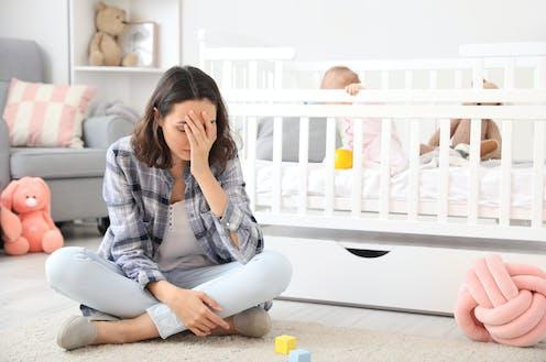 Mujer apesadumbrada sentada en el suelo junto a una cuna con un bebé.