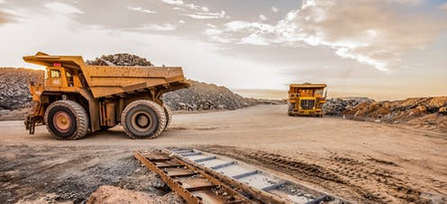 Dump trucks transporting platinum ore for processing at a dusty mining site.