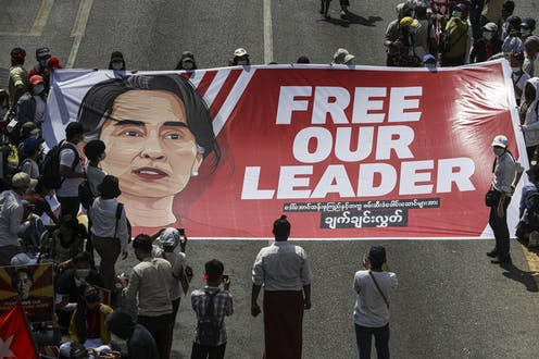A crowd of protesters holds a large banner demanding the release of Myanmar's de facto leader Aung San Suu Kyi.