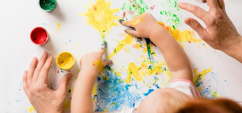 Parents finger painting with their child.