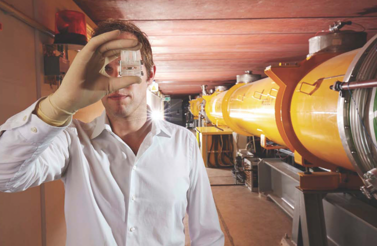 A man holds a clear component in front of his eye. Behind him is a large yellow pipe