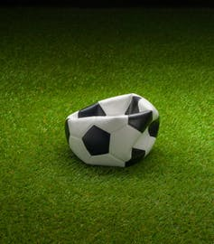 Punctured football on grass