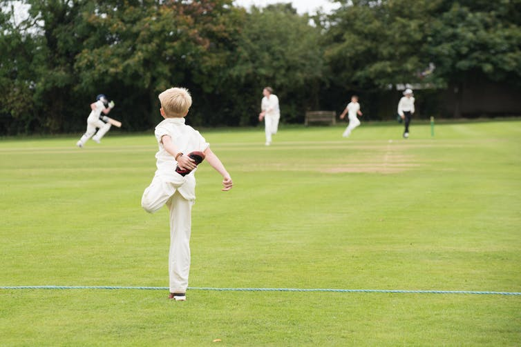 A boy dressed for playing cricket stretches his leg, with other players in the background.