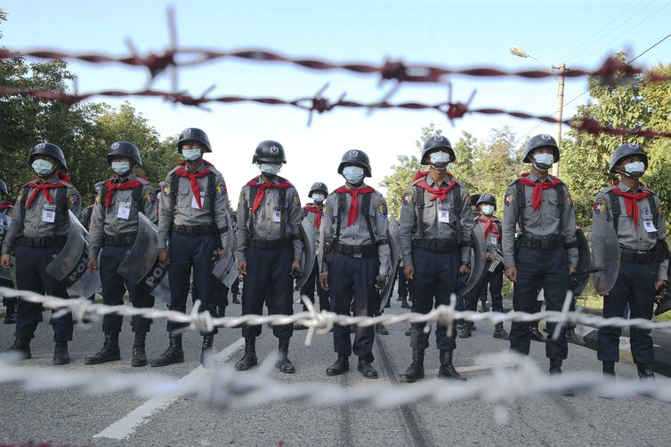A row of police in riot gear stand behind barbed wire.