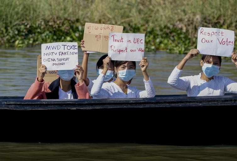 Women in masks carry placards as they sit in a boat.