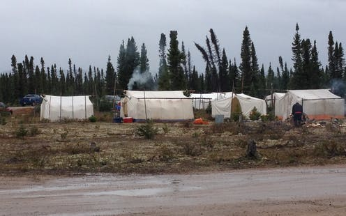 A gathering place with large white tents with tall trees in the background