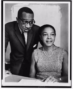 Two Black scientists sit together while conducting their research.