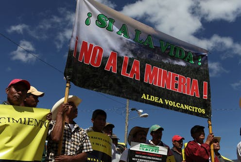 Protesters hold up an anti-mining sign.