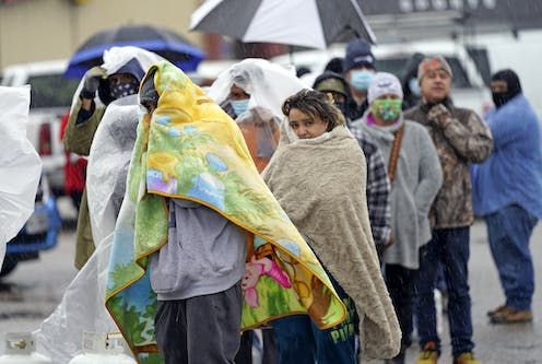 People lined up outdoors wrapped in blankets