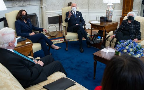 Biden sits with Harris and Yellen in the Oval Office, all wearing masks.