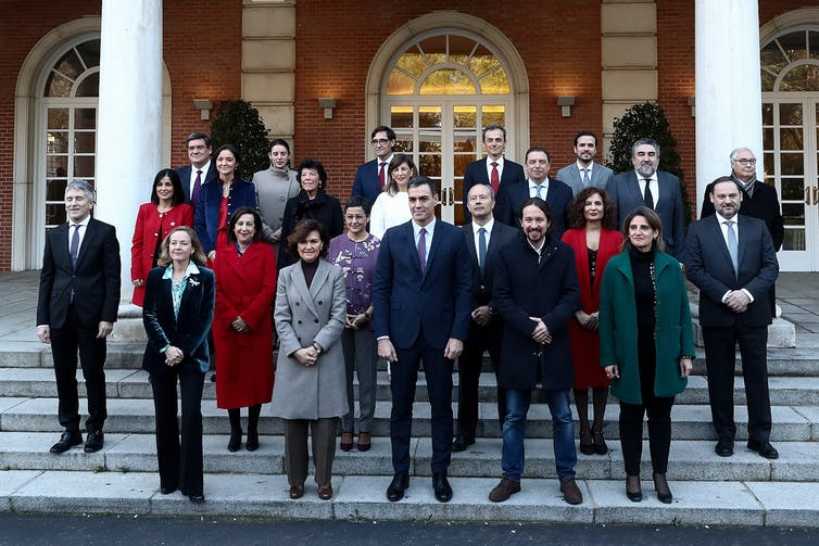 Group photo of Spanish cabinet standing on white steps with Sanchez in middle, surrounded by a gender-diverse group