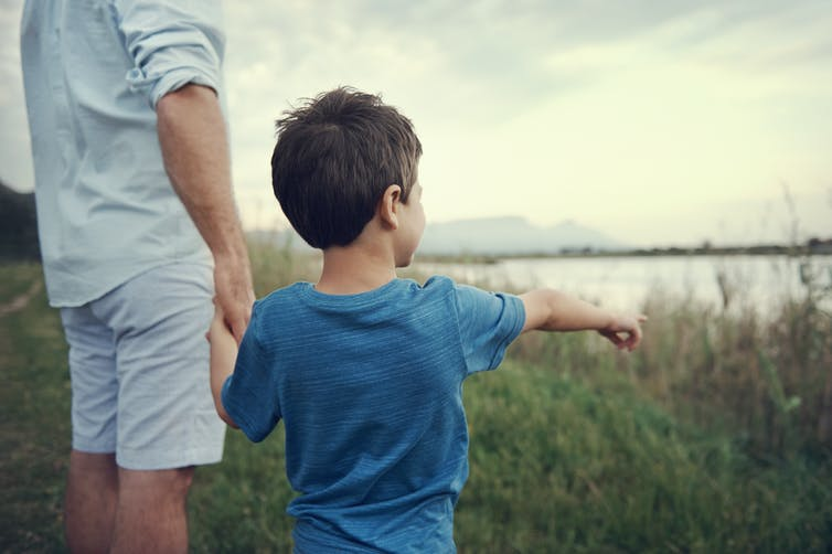 Young boy pointing to something, while holding his fathers hand. They're standing in front of a lake.