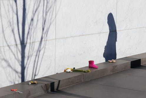 Personal items and a woman's shadow next to Christchurch earthquake memorial wall