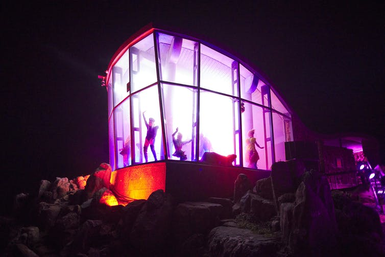 Performers inside pink light-filled enclosed stage