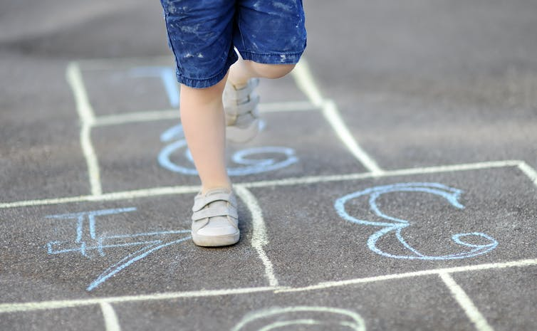 Kid's feet on hopscotch grid.