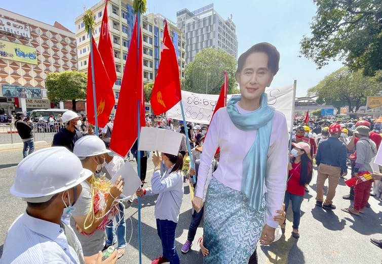 Coup protesters hold poster of Aung San Suu Kyi