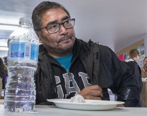 Chief Rudy Turtle sitting at a table with a water bottle and an empty plate in the foreground.