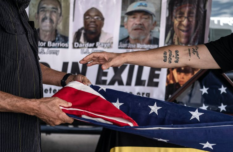 Arms fold an American flag; in background, pictures of 'veterans in exile'