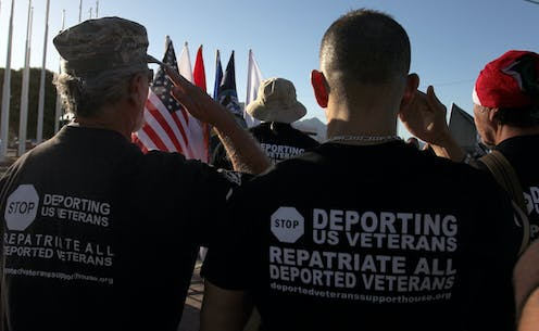 Men wearing shirts advocating for deported veterans are pictured from behind, saluting an American flag