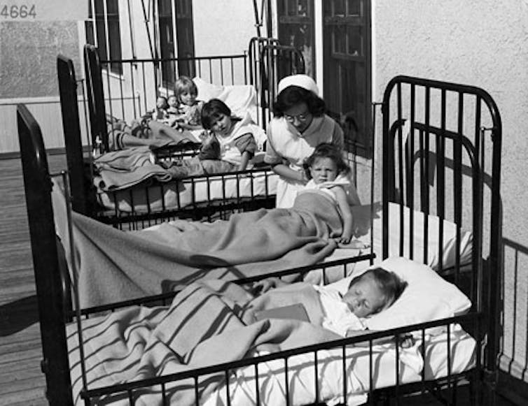 Black and white photograph of children in a row of hospital beds with an attending nurse.