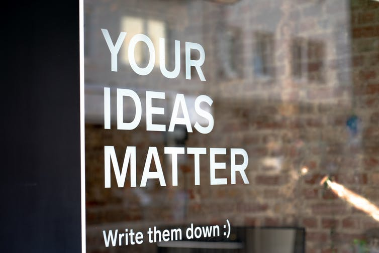 A sign reads Your Ideas Matter on a glass office door.