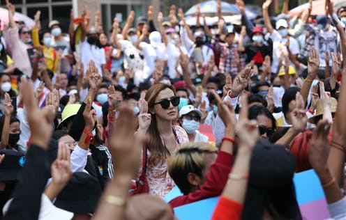 Anti-coup protesters flash the three-fingered salute during a rally