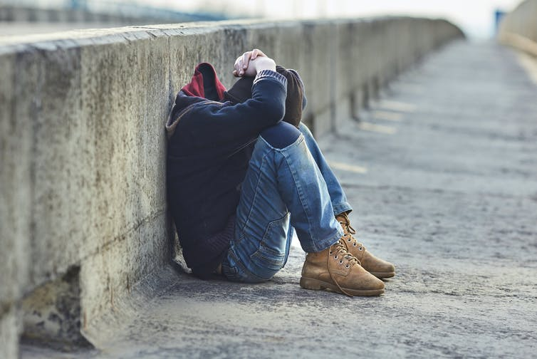 A homeless youth holds their head while sitting on the ground.
