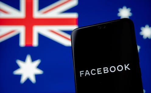A phone with Facebook written on it in front of an Australian flag