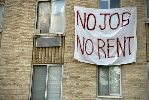 "A banner on an apartment building that reads ""No job, no rent."""