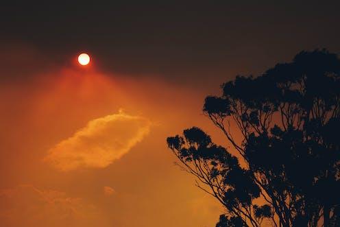 A red sun shines through smoke haze